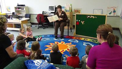 Children's services librarian reads to children during a storytime session. Children sit in a half circle on the floor.